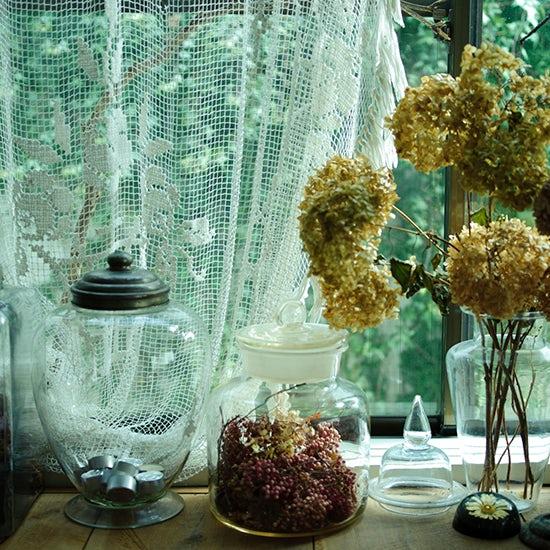 あちこちで見つけた古いガラス瓶には、自宅で飾りながら、自然にドライフラワーになった紫陽花などをディスプレイ